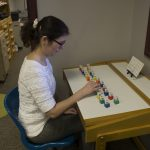 A patient concentrates on a vision therapy activity designed to improve hand-eye coordination.